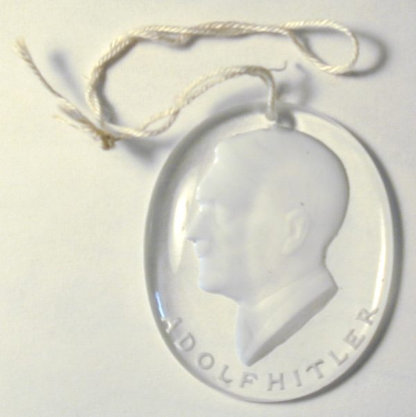 """Glass Hitler Medal from the 20 piece """"Famous Germans"""" set (see below). 36 mm tall by 30 mm wide."""